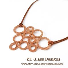 Copper and leather bib necklace featuring a variety of textured circles on soft and velvety leather cords.