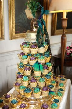 Egyptian Party : Peacock themed cupcake display : Beautiful green, purple, blue, and black cupcakes in gold liners on a multi-tiered display