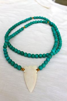 Turquoise and gold beaded necklace with a bone arrowhead pendant