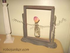 Suspended Bud Vase by Margo       This is a really easy project. First find an old photo frame that is on a stand. That will be the hardest part. Wrap wire around an old bottle, then extend the wire on both sides and wrap around the sides of the frame several times. Then use a pencil and curl the wire. Add pearls, or buttons to the bottle and your favorite flower.