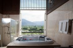 Bathroom with amazing view of the outdoors with design of polished porcelain tiles in a peach/cream shade