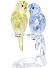 """This pair of budgies sparkles brilliantly in pastel yellow and lavender-colored crystal. They perch on a clear crystal branch for a lively effect. 
