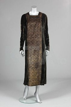 A Mariano Fortuny stencilled black velvet evening gown, circa 1920-30, with circular label to beige satin lining, the front and back stencilled in gold with interlocking geometric strapwork repeats with islamic calligraphy borders, the sleeves and sides inset with pleated black silk adorned with Murano glass beads