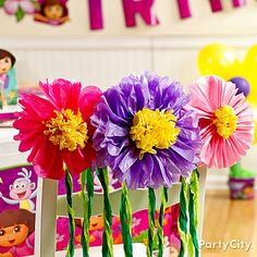 Easy DIY tissue paper flowers and jungle vines made from streamers turn the room into Dora's lush, blooming rainforest world! See more in our Dora the Explorer Birthday Party Ideas Guide.