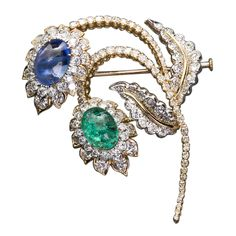 A wonderful diamond in 18k yellow gold flower brooch with one large cabochon emerald and cabochon sapphire of fabulous color and brilliance by David Webb. 20th Century