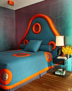 For a granddaughter's bedroom, Mattia Bonetti dreamed up a fantastical headboard and matching bedspread with orange calfskin accents. He also designed the walls' hand-painted circular motif as well as the cast-bronze table lamp.