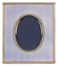 A FABERGÉ SILVER PEARL SET AND GUILLOCHE ENAMEL PHOTOGRAPH FRAME, WORKMASTER MICHAEL PERCHIN, ST. PETERSBURG, 1899-1908. Of rectangular form, the oval aperture set with half pearls, beveled glass inside a field of translucent sky blue enamel over a wavy engine turned ground, with laurel borders and foliate corners.