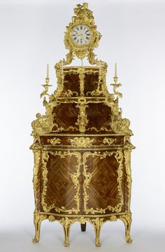 Corner Cupboard; Cabinet by Jacques Dubois (French, 1694 - 1763, master 1742), clock movement by Étienne Le Noir II (French, 1699 - 1778, master 1717), clock dial enameled by Antoine-Nicolas Martinière (French, 1706 - 1784, master 1720), et al; Paris, France; about 1744 - 1755; dial 1744; Oak, mahogany, and spruce veneered with bloodwood, tulipwood, wamara, and kingwood; gilt-bronze mounts; enameled metal clock dial; glass.