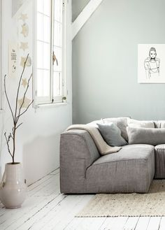 Goeie kleur op de muur. Mooi bij wit en zacht grijs - White, grey and light interior / living room with white wooden floors and a grey wall, grey canvas vtwonen couch Lazy, a big off-white vase by Nijhof, natural rug Zuiver and accessoires by Sukha Amsterdam, All the Luck in the World, Studio Elke van den Berg , H&M Home, Het Kabinet, Bodilson, Six and Sons, The Cherry on Top, Livv Lifestyle and De Oude Plank. | Styling Kim van Rossenberg | Photographer Sjoerd Eickmans | vtwonen May 2015