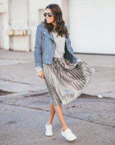 A moto jacket over a crew neck sweater, a silver pleated skirt, and sneakers.