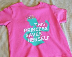 This powerful tee is exactly what your little princess needs to show the world that she is a strong and amazing girl. Our made-to-order shirt features teal, white and holographic artwork on a pink t-shirt or onesie. It features the phrase this princess saves herself with a strong princess silhouette in the background. The princess crown is shiny holographic. Be sure to review the size chart (see shop policies) to ensure you get the correct size. When in doubt, size up!   All of our products…