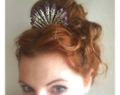 A beautiful two inch handmade crystal comb - perfect for tucking into the back of your hair to hold your veil for a perfect, alternative bridal look. Shining blue raw titanium crystals make the perfect back-drop for tiny stars and branch details. An icy, woodlandy piece for any ice queen. DEMETER is the Goddess of Winter. You can be too! Available in gold or silver, and in a variety of lengths. Cant find what you need? Contact us to design something just for you. The stones in this comb can…