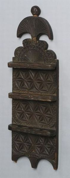 """Carved Wooden Spoon Rack, eastern United States, 1766, carved head finial on three-tiered rack with shaped back, chip-carved  rosettes and fan decorations, inscribed conjoined initials """"IVP"""" and year """"1766"""" on top of one tier, each rack holds four spoons, (a few small losses on bottom), ht. 24 x 7 3/8 in.   Sold for $ 14,100"""