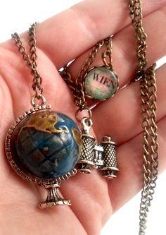 Eine wunderbare lange Kette altbronze mit einem Globus (3cm Höhe) einen Fernrohr und eine kleine Medallie (ø 12mm), in dem die Karte und Name de...
