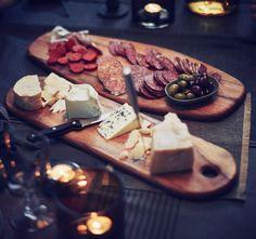 Zwei SITTNING Schneidebretter aus massiver Akazie, eines belegt mit Käse, das andere mit Wurst