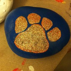 Auburn tiger paw painted rock with glitter.
