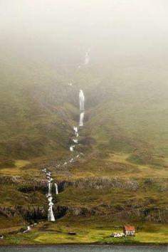 Uma cachoeira sem nome escorre ao lado de uma pequena casa na costa leste da Islândia por minerva