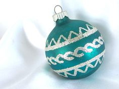 This beautiful matte teal / turquoise Shiny Brite Christmas ornament has a geometric chevron and swirl design in silver glitter.