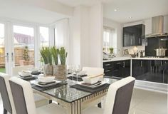 Interior Designed small kitchen / dining room, using black gloss units encased in white.  Upholstered chairs and glass table. Large format kitchen tiles, well done !  Barratt Homes (The Somerton) in Gloucester.