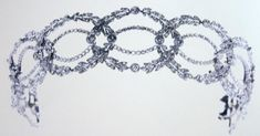 A diamond tiara of double, interlocking oval wreaths. The other oval is of laurel leaves, punctuated with circular diamonds to interlock with the inner wreath.