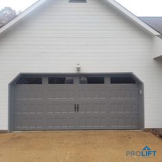 Don't overlook your garage door when it comes to maximizing your home's style for curb appeal and achieving that first-impression's 'WOW' factor. Shown here: Low maintenance, insulated garage door in soft gray with recessed panels, long top row windows and decorative black handles. | What Homeowners Need To Know In 2021 by ProLift Garage Doors Blog Garage Door Cost, Garage Door Maintenance, Single Garage Door, Garage Door Panels, Modern Garage Doors, Garage Door Springs, Garage Door Styles, Overhead Garage Door, Garage Door Repair
