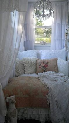 Beautiful shabby chic vignette - love the quilt, lacy pillows, embroidered pillows and lace appliqued curtains, chenille, and the chandelier - the chippy metal dog is the perfect accent - from All Things Shabby and Beautiful via tumblr