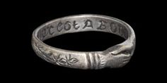 Medieval 'mon coeur est a vous' Clasped Hands Silver Posy Ring, Circa 15th-16th century AD. A love ring with clasped-hands motif on the external surface between engraved branches; engraved on the internal surface in Lombardic script 'mon coeur est a vous' (my heart is yours) between starbursts.