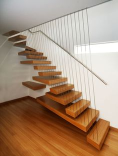 Sliced stair. The treads have angled edges, guarded by cables at the same angle with interesting oversized tread arrangement behind the staircase.