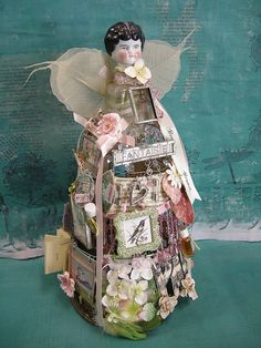 skirt frame covered with bits and pieces of ephemera, found objects, glass charms, tiny books, beads, vintage porcelain doll head and bottle