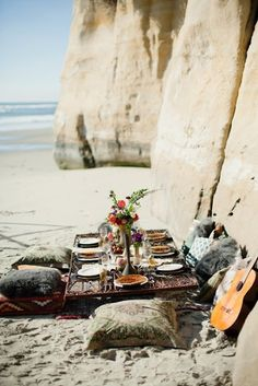 Boho beach picnic with pillow top table in the sand and guitars against the rocky cliff