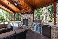Covered outdoor living area with grill, refrigerator, and fireplace.