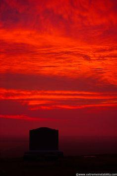 Hazy red sunrise behind a tombstone in eastern Nebraska.