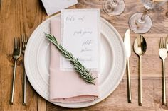 Simple, rustic, wedding tablescape- gold flatware, white charger, blush linens, with rosemary sprig accent on farmtable. Unique wedding menu inspiration. Willowdale Estate is a weddings and events venue on the Northshore. Willowdaleestate.com | Alicia Ann Photography