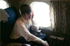 John Lennon sitting in a window seat on an airplane headed from St. Louis, Missouri on August 21, 1966 to New York City for the Beatles' concert at Shea Stadium.
