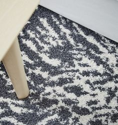 A close-up image of a gray and white rug, with a natural wood coffee table.