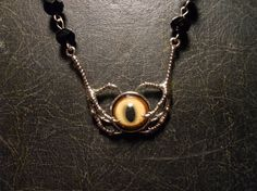 """Talons Clutching Glass Cat Taxidermy Eye Rosary by TheCuriositeer. The necklace has """"a 14mm Taxidermists cat eye, intended for a small bobcat mount. This is a full, real, competition quality taxidermists eye."""" - $36.00"""