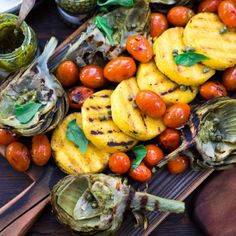 Grilled artichokes and polenta with pesto, capers, blistered tomatoes and basil served family style! Vegan and gluten free