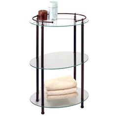 Premier Oval Glass Taboret - Three Shelves - Burnished Bronze by Gatco. $252.95. This glass taboret will be a beautiful addition to your modern or traditional bath. The three shelves are the perfect spot for bath products and hand towels, and the brass accents are available in several premium finishes. The ball tip accents also create a functional ring holder on the top shelf. 19 L x 12 W (front to back) x 31 H. Metal accents made of solid forged brass. Shown in Burnished B...