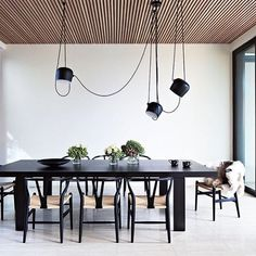 Midcentury modern dinning space with a large exposed cord chandelier, a black table and wishbone chairs