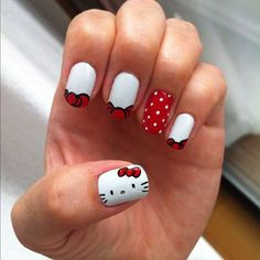 Peek a boo, I see a red ribbon, who is it? It's Hello Kitty! A very cute and candid nail art design incorporating red and white shades. A red nail is further highlighted with adorable dots of white.