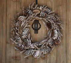 Real pinecones and faux pine branches are sprinkled with frosty layers of glitter on this snowy indoor/outdoor wreath.