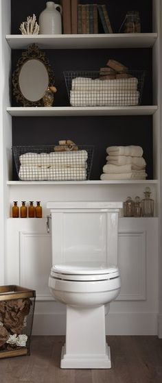 love shelves above the toilet to maximize space in a small bathroom.  I love the black background, books and decorations, and the wainscoting shelf!