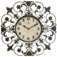 """This elegant iron wall clock, features a very decorative frame with fleur de lis designs. The dial is tan with black Arabic numbers at every hour. Black metal hands. Operates on a highly accurate quartz movement and one """"AA"""" battery, not included. Guaranteed by a one year manafacturer's warranty."""