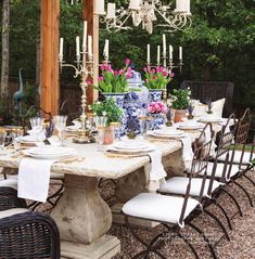 Whimsical garden features a French style concrete dining table seating eight wrought iron dining chairs with white cushions and two wicker host chairs illuminated by a chandelier hung from a pergola. Chandelier For Long Table French Country Dining Room, Modern French Country, French Country Decorating, French Country Porch, Country Patio, French Patio, French Dining Chairs, Country Blue, Concrete Dining Table