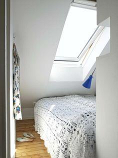 Sengen er plassert helt inntil skråtaket, slik at dagslyset kommer gjennom vinduet og treffer sengen. Sengen er dekket av et heklet sengeteppe.