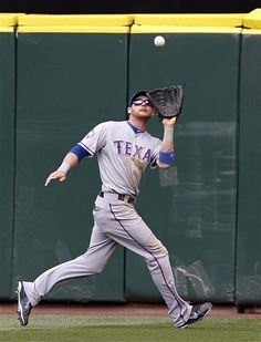 Texas Rangers center fielder Craig Gentry catches a fly ball from Seattle Mariners' Casper Wells in the fifth inning of a baseball game Sunday, July 15, 2012, in Seattle. The Rangers won 4-0. (AP Photo/Elaine Thompson)