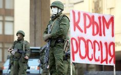 Heavily-armed soldiers without identifying insignia guard the Crimean parliament building next to a sign that reads: 'Crimea Russia' in Simferopol, Ukraine