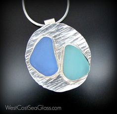 """Two sea glass blues which have each been on their own unique journey at sea seem to be just perfect for eachother. The colors in this pair juxtapose yet dance together in this one of a kind, sea glass focal piece. The aqua blue and cornflower blue teardrop shaped pieces each measure just over 5/8"""". They are bezel set in fine, anti tarnishing silver and soldered to a 1.25"""" artisan hammered sterling silver circle. It is strongly soldered to a handmade fine silver """"slide"""" bail that has a 3/8""""…"""
