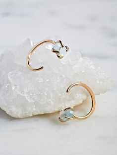 Raw Aqua Ear Hugging Hoop | Beautifully dainty 14k yellow gold ear hugging hoops made in America. Featuring raw aqua stones and subtle backings for a secure fit.