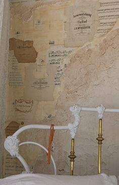 wall treatment at Posh on Palm, Sarasota FL... vintage sheet music and book pages under rough plaster